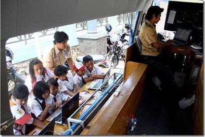 MELEK INTERNET - Sejumlah siswa SDN Sumberejo 01 asyik berselancar di dunia maya pada Mobile Pelayanan Internet Kecamatan (M-PLIK) yang diparkir di Balai Desa Sumberejo, Kec/Kota Batu, Rabu (24/10/2012). Meski rata-rata adalah anak petani, belasan siswa ini terlihat mahir membuka youtube, jejaring sosial dan game online. SURYA/HAYU YUDHA PRABOWO